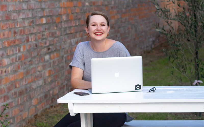 A young woman with short brown hair sits on an outdoor picnic bench with her laptop. She's smiling at the camera.