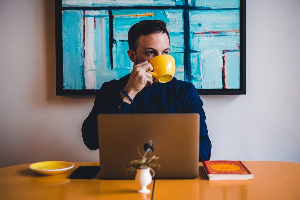 a man sits at a desk with a laptop in front of him. He's sipping coffee from a large yellow mug.
