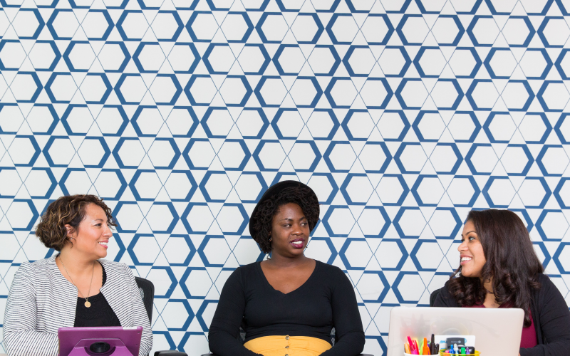 Three women sit together at a boardroom table, they're looking towards each other and speaking. Behind them is a blue and white patterned wall.
