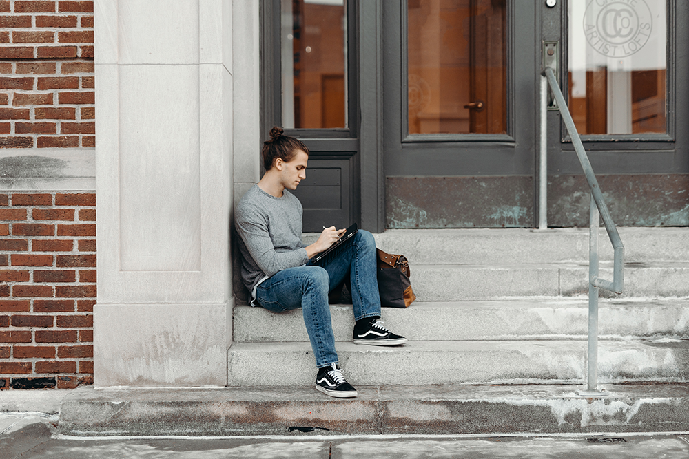 A man sits on the steps in front of a building. He's working on an ipad. He's wearing jeans, black and white Vans trainers and a grey long sleeved top.