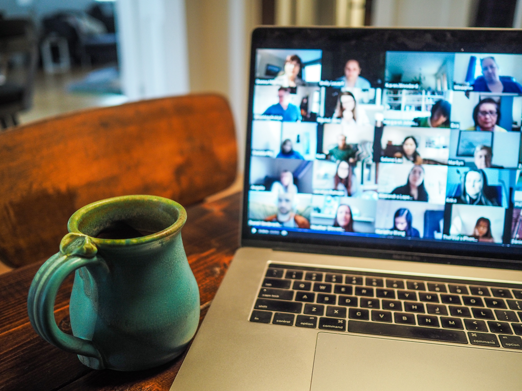 A laptop is on the table. On the screen, you can see a full team on a video call.